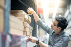 Asian man using tape measure on cardboard box. Young Asian man worker using tape measure for measuring dimension of product in cardboard box. Shopping lifestyle Stock Photography