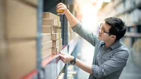 Asian man using tape measure on cardboard box. Young Asian man worker using tape measure for measuring dimension of product in cardboard box. Shopping lifestyle royalty free stock photos