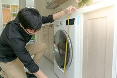 Asian man using tape measure on washing machine. Young Asian worker man using tape measure for mesuring washing machine in kitchen counter. Home interior design Stock Photography