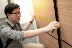 Asian man using tape measure on wooden closet. Young Asian man using tape measure for measuring modern wooden cabinet in walk-in closet showroom. Shopping royalty free stock photography