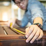 Asian man using tape measure on wooden table. Young Asian man using tape measure for measuring wooden outdoor table in showroom. Shopping furniture for home stock images