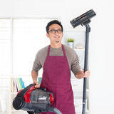 Asian man vacuuming Stock Images