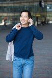 Asian man walking with cellphone Royalty Free Stock Image