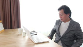 Asian Man Walking Into The Frame And Working With Laptop. stock footage