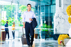 Asian man walking in hotel lobby Stock Photography