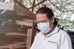 Asian man wear face mask medical protection in wood factory Royalty Free Stock Photography