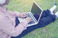 Asian man wear pink shirt while listening to the music by ear plug and typing Thai keyboard of laptop sitting on  green grass. Relaxing in the park Stock Photo