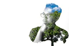 Asian men wearing eyeglasses are thinking of something, Double exposure. Asian man wearing eyeglasses are thinking of something, Double exposure, trees and blue royalty free stock photo