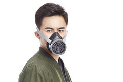 Asian man wearing gas mask. Young asian man wearing gas mask staring at camera, isolated on white background Stock Photo