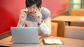 Asian man wearing glasses while using laptop royalty free stock photography