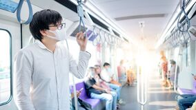 Free Asian Man Wearing Mask Holding Handrail On Skytrain Royalty Free Stock Images - 182732219