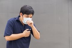 Asian man wearing mouth mask against air pollution. Asia male wear mask protection useing smartphone., copy space for text Royalty Free Stock Image