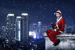 Asian man wearing santa claus costume sit on the rooftop. Christmas present Stock Photography