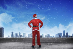 Asian man wearing santa claus costume standing on the building rooftop. Looking the city Stock Photos