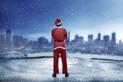 Asian man wearing santa claus costume standing on the building rooftop. Looking the city Royalty Free Stock Photography