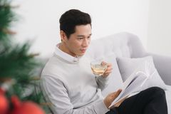 Asian man wearing sweater drinking tea at home during christmas.  Royalty Free Stock Photo