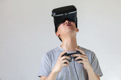 Asian man wearing VR goggle and immersing himself in VR gaming Stock Photos