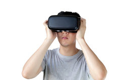 Asian man wearing VR goggle and immersing himself in VR multimedia. In white isolated and clipping mask. VR is simulation of a physical presence in places in stock photography