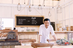 Asian man wearing a white shirt standing in Bakery shop Royalty Free Stock Image