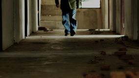 An Asian man wears a hoodie, obscuring his face and holding a rope inside a desolate building.