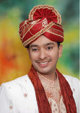 Asian man in wedding clothes. Portrait of happy young Asian groom in traditional silk wedding clothes with turban; colorful studio background Royalty Free Stock Photos