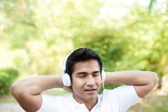 Asian Man with white headphones enjoying Stock Image