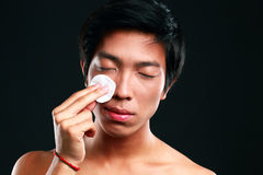 Asian man wipes his face with cotton pad Stock Photo