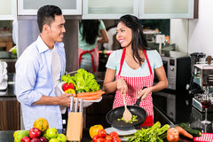 Asian man and woman cooking together Stock Images
