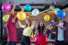 Asian man and woman having fun in Christmas party, dancing and playing balloons at the restaurant royalty free stock photos