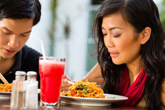 Asian man and woman in restaurant Stock Photo