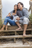 Asian Man Woman Romantic Couple on Beach Steps. Young Asian Chinese men & woman, boy & girl, couple sitting on wooden steps overlooking a beach drinking mugs of Royalty Free Stock Image