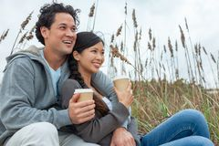 Asian Man Woman Romantic Couple Drinking Takeout Coffee on Beach royalty free stock photos