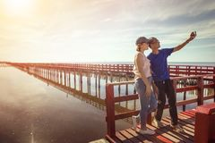 asian man and woman taking a photo on red wood bridge against sun rising sky stock photo