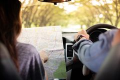 Asian man and woman using map on road trip and Happy young couple with a map in the car. Blurred and Soft focus stock photography