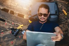 Asian man  working and checking photo on laptop at outdoor nature and He is relaxing, enjoying on travel royalty free stock image
