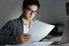Asian Man Working with Documents at Night Stock Photo