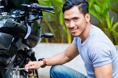 Asian man working on his motor scooter Stock Photography