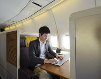 Asian man working with laptop on first class airplane Royalty Free Stock Photography