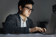 Asian Man Working with Laptop at Night royalty free stock photos