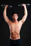 Asian man working out with dumbbell Royalty Free Stock Photography