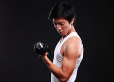 Asian man working out with dumbbells. On black background Stock Photo