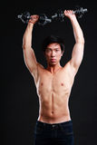 Asian man working out with dumbbells. On black background Royalty Free Stock Photos