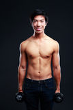 Asian man working out with dumbbells. Happy asian man working out with dumbbells on black backgroung Stock Photo