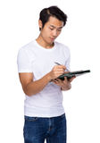 Asian man write on clipboard Royalty Free Stock Images