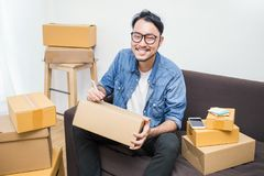 Asian man writing address on the box. Start up small business entrepreneur SME, asian man writing address on the box. Portrait of young Asian small business Stock Image