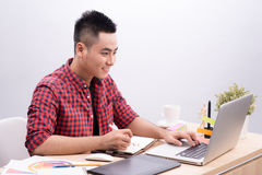 Asian Man Writing At Desk In Busy Creative Office Stock Photos