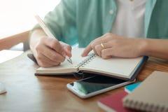 Asian man writing text on notebook Stock Photos