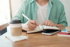Asian man writing text on notebook Stock Photography