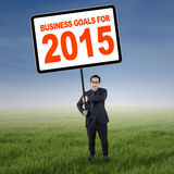 Asian manager with business goals for 2015. Young entrepreneur standing at field and holding a board with a text of business goals for 2015 Royalty Free Stock Photos