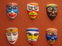 Asian masks. Colorful Asian masks displayed on an amber wall Royalty Free Stock Photography